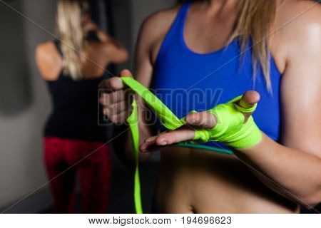 Mid-section of woman tying hand wrap on hand in fitness studio