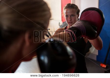 Female boxer punching mitts with instructor in fitness studio