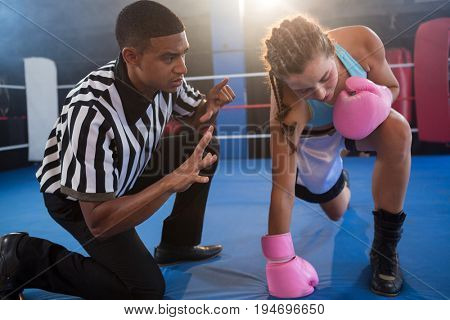 Referee gesturing to female boxer in boxing ring at fitness studio