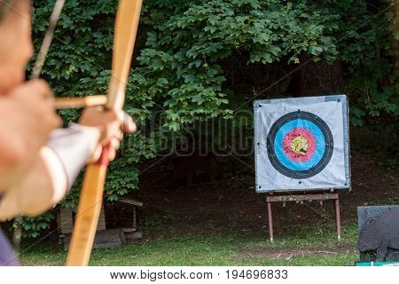 archer pulls bowstring aiming arrow at sport aim