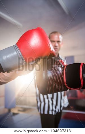 Close-up of boxers punching fists against referee at fitness studio