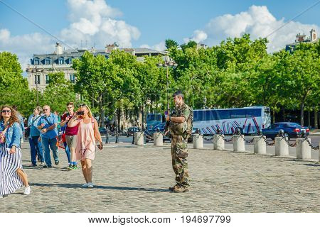 PARIS, FRANCE - JULY 2, 2017: soldier of national Armed Forces of France, guarding tourists at the center of Place Charles de Gaulle with Arc de Triomphe.