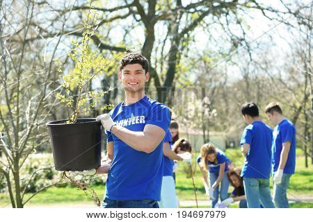 Handsome young volunteer with team outdoors