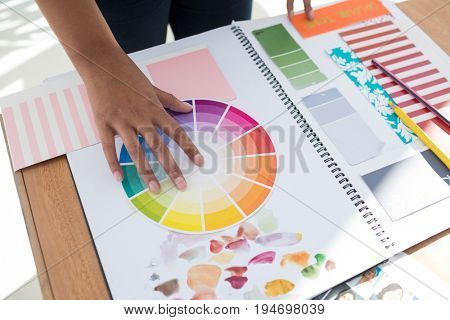 Graphic designer holding color swatch at desk in the office