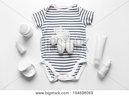 Composition of bodysuit, crochet toy and baby care accessories isolated on white