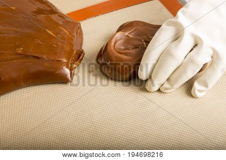 Artisanal production of caramel toffee sweets butterscotch candies. Woman with white lab coat blouse cutting rolls of sugar pastry to do butterscotch candies traditional sweetx of France