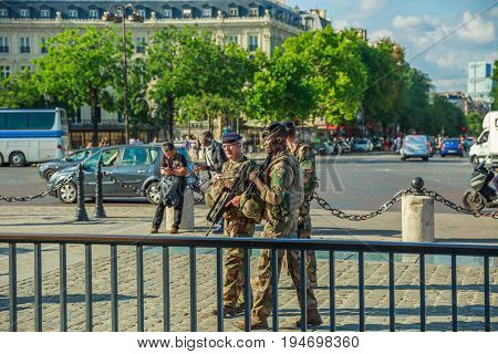PARIS, FRANCE - JULY 2, 2017: soldiers of French Armed Forces of France, keeping security after recent terrorist attacks in Paris. Arc de Triomphe at the center of Place Charles de Gaulle.