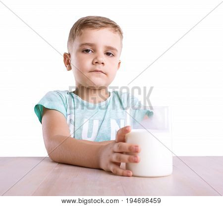 Close-up portrait of amazing boy drinks a glass of milk isolated on white background. Curious little kid wearing blue t-shirt with a glass full of nutritious milk isolated on a white background.