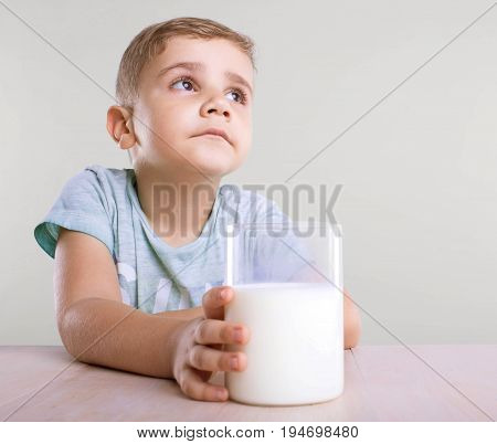 An enormous glass full of healthful tasty milk in a hand of an adorable and sad tiny kid with a blond hair, in a blue T-shirt, isolated on a gray background.