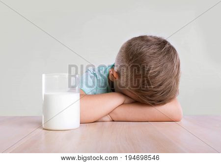 A tiny cute little boy in a blue t-shirt is sitting near to the transparent glass full of organic milk. The handsome little boy with a glass full of tasty milk, on a gray background.