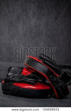 Close-up of boxing gloves and focus mitt in fitness studio