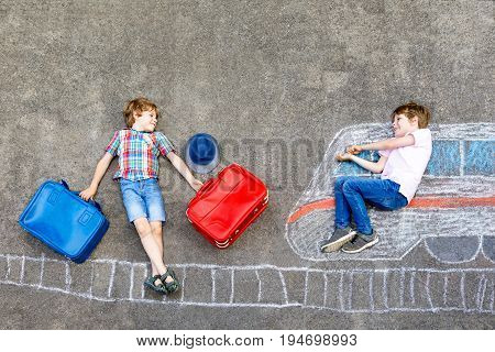 Two little kids boys having fun with train picture drawing with colorful chalks on ground. Children having fun with chalk and crayon painting and game going on vacations. Friends with suitcases.