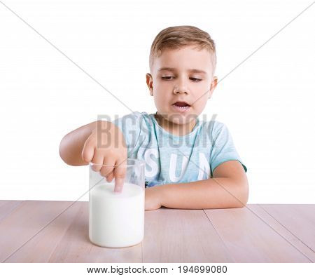 A curious small with a blonde hair kid in a light blue T-shirt is dipping his tiny finger in a huge glass full of tasteful organic milk on a bright brown table, isolated on a white background.