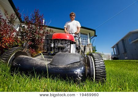 A man mowing the front lawn with focus on the front