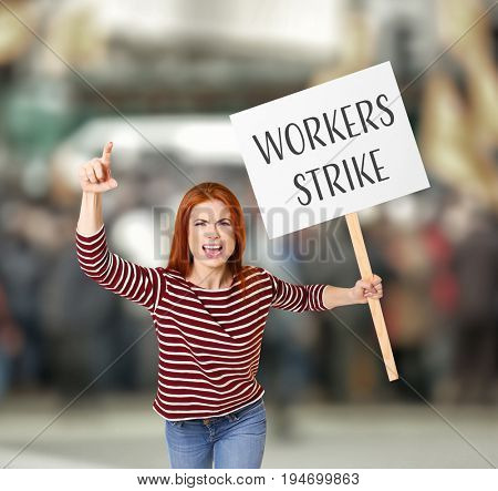 Young woman with signboard and blurred crowd on background. Workers strike concept