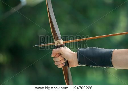 female archer hand keeping bow aiming arrow to the target