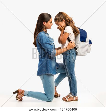 Mother comfort her little daughter on her first day of school
