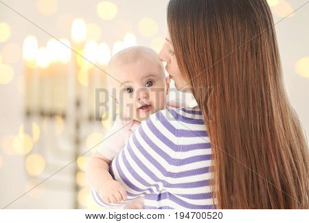 Mother with little child on blurred festive lights background. Baby's First Hanukkah