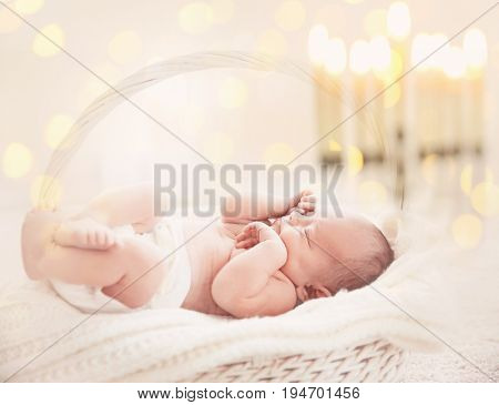 Little child in basket on blurred festive lights background. Baby's First Hanukkah