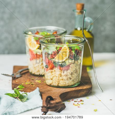 Healthy vegan salad with quionoa, avocado, dried tomatoes, basil, olive oil, mint in glass jars, marble background, selective focus, copy space, square crop. Clean eating, vegan, detox food concept