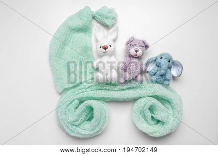 Cute woolen toys and clothes in shape of baby carriage isolated on white