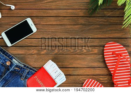 Summer vacation concept. Composition with mobile phone and documents on wooden background