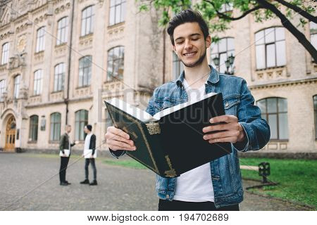 Smiling student in jeans jacket reading a huge book in front f the camera and holding it with both hands standing near the college. Close up