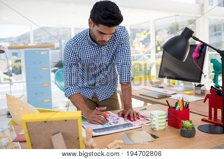 Male graphic designer working at desk in the office