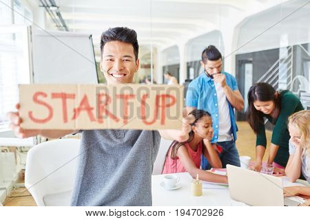Start-up founder with business team holding sign