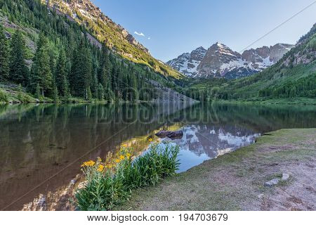 a scenic evening reflection of the maroon bells in maroon lake in summer