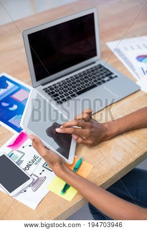 Female executive using digital tablet at desk in the office