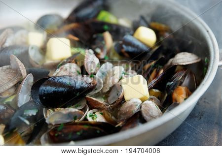 Clams and mussels fried with melting butter on hot pan at commercial kitchen