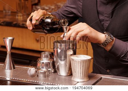 Bartender is pouring alcohol into a mixing glass