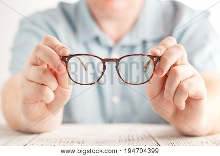 optometrist giving new glasses hold it in both hands