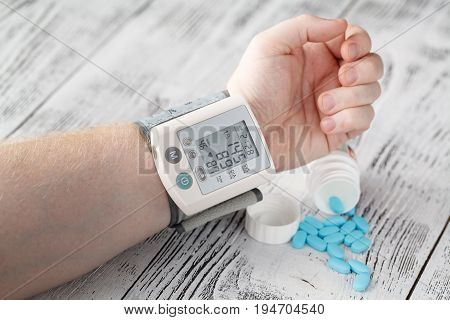 Tonometer High Blood Pressure Indication On The Male's Arm. Hypertension Medical Pills On The Backgr