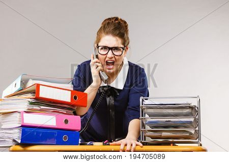 Mobbing at work bad job relations concept. Angry mad bossy businesswoman talking on phone sitting working at desk full off documents in binders.