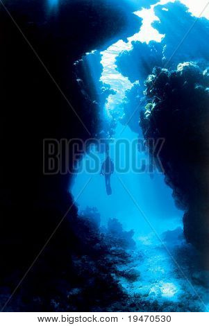 Silhouette of a diver with sun rays through a cave