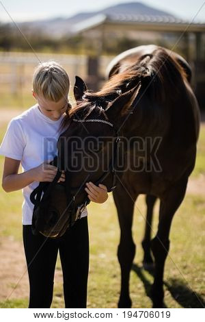 Smiling girl caressing the horse in the ranch on a sunny day