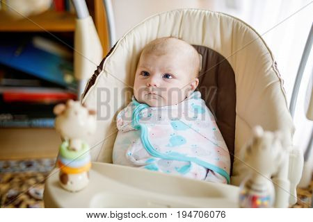 Cute adorable newborn baby sitting in swing. Closeup of peaceful child, little baby girl swinging and playing. Looking on toys. Family, birth, new life. Attentive child. Tiny girl wrapped in blanket
