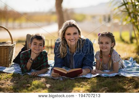 Portrait of smiling mother and kids reading novel in park on a sunny