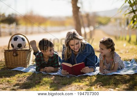 Mother and kids reading novel in park on a sunny