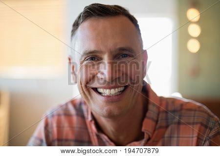 Close-up of man smiling at camera in restaurant