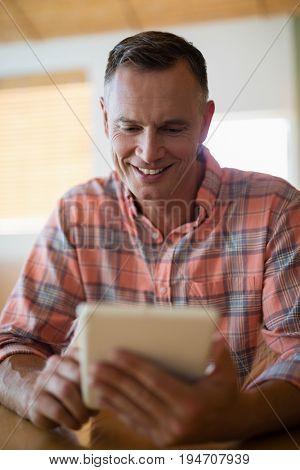 Smiling man using digital tablet in restaurant