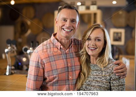 Portrait of happy couple standing together with arm around in bar