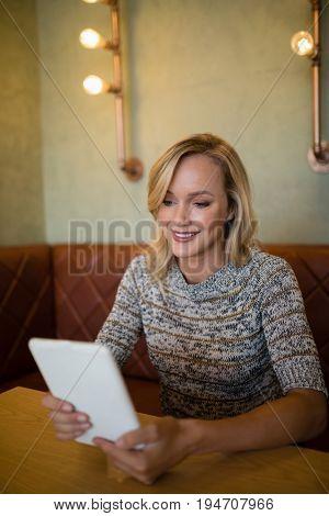 Smiling beautiful woman using digital tablet at table in bar