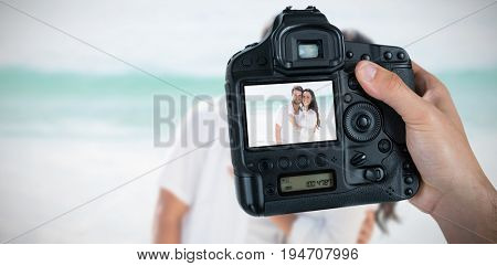 Composite image of cropped hand of photographer holding camera