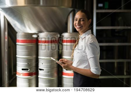 Portrait of smiling waitress using digital tablet in bar