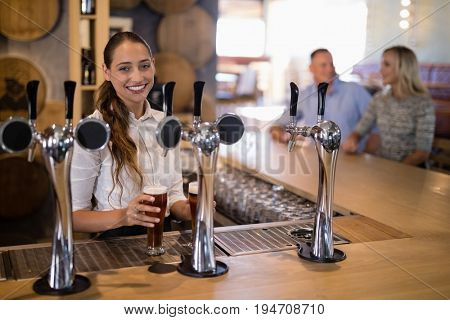 Portrait of female bartender holding glass of beer at bar counter