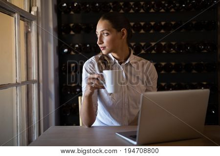 Thoughtful woman looking through window while having coffee in café