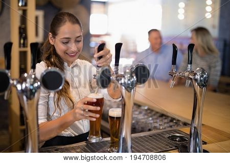Smiling female bartender filling beer from bar pump at bar counter